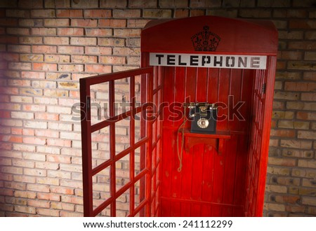 Open wooden replica of an iconic red British telephone booth with a vintage dial-up telephone, sign and crown against a brick wall - stock photo