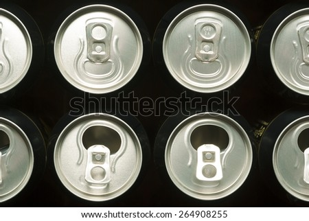 opened and closed canned drinks in black  - stock photo
