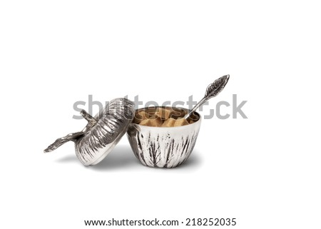 Opened apple shaped sugar container with brown sugar cubes and a spoon leaf - stock photo