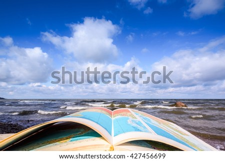 Opened atlas book on the seashore - stock photo