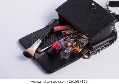 Opened bag with scattered cosmetics. - stock photo