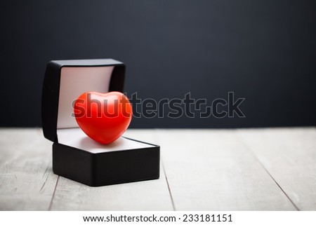 Opened black leather covered gift box with red heart on white wooden table.  Selective focus.