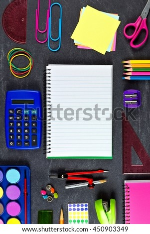 Opened blank lined school notebook with frame of school supplies over a chalkboard background - stock photo