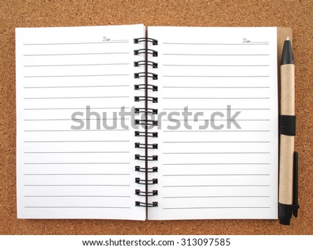 Opened blank notebook with pen on wooden background.