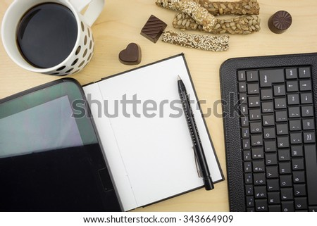 Opened blank notebook with tablet, pen, keyboard  and cup of coffee, on wooden desktop. - stock photo