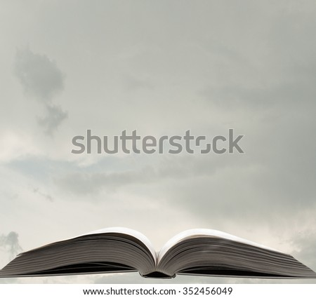 Opened book among many others on sky background