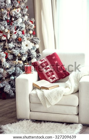 Opened book and a cup of tee on the cozy armchair with warm blanket and cushion on it near Christmas tree - stock photo