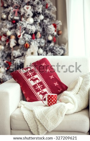 Opened book and a cup of tee on the cozy chair with warm blanket and cushion on it near Christmas tree - stock photo