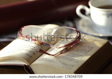Opened book and glasses, on old wooden table. - stock photo