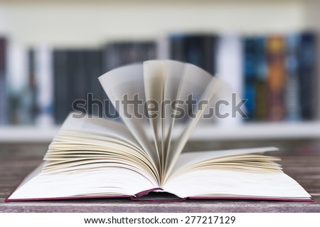 Opened book in front of bookcase with flying pages and motion blur with selective focus. - stock photo