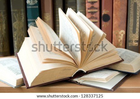 Opened book lying on the bookshelf - stock photo