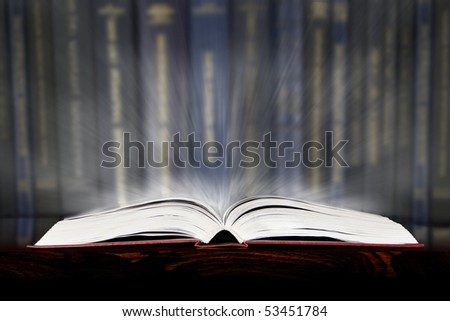 opened book, lying on the bookshelf with a lot of knowledge and secrets - stock photo