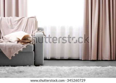 Opened book on comfortable sofa against window in the room - stock photo