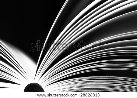Opened book on dark background - black and white version - stock photo