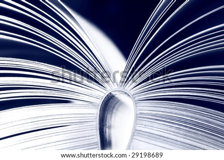 Opened book on dark background - colored blue - stock photo