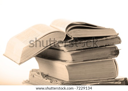 Opened book on stack of old books. White background. Shallow DOF. - stock photo