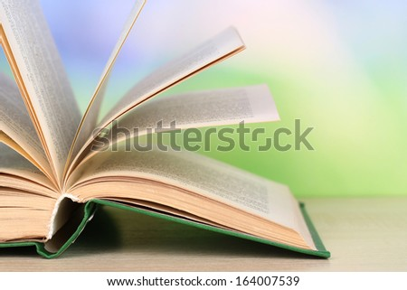 Opened book on wooden table on natural background
