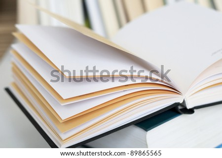 Opened book with empty pages on other book in books background