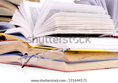 opened books and glasses on table front of a full bookshelf - stock photo