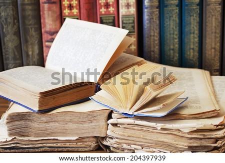 Opened books lying on the bookshelf - stock photo
