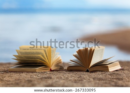 Opened books on a beach - stock photo