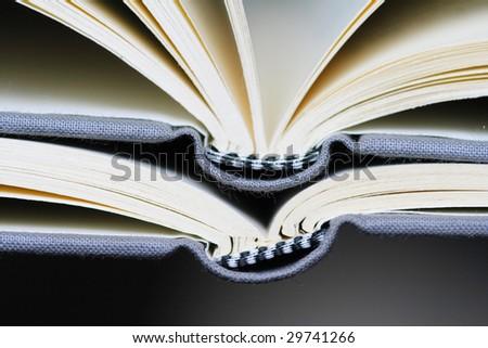 Opened books on dark background - stock photo