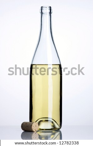 Opened bottle and glass of white wine with cork