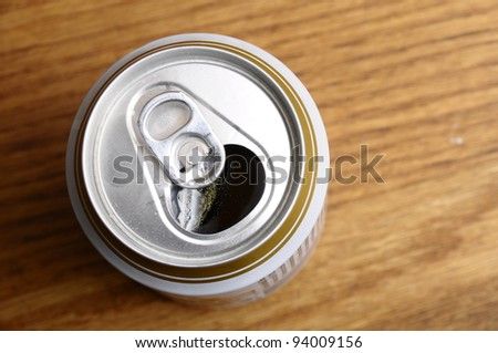 Opened Can of beer on wooden table. Top view - stock photo