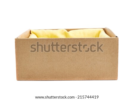 Opened cardboard box with the yellow cloth inside, isolated over the white background, side view - stock photo