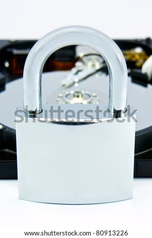 "Opened computer hard disk ""locked"" with a padlock - stock photo"