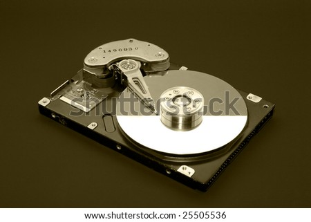 Opened computer hard drive isolated on black (sepia) - stock photo