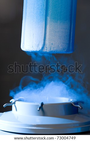 Opened container with liquid nitrogen, blue light and vapour - stock photo