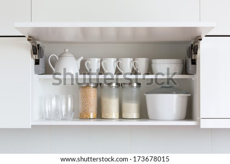 opened cupboard with kitchenware inside - stock photo