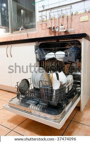 Opened dishwasher in the kitchen. - stock photo