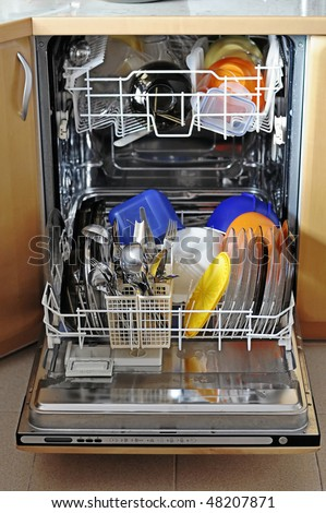 opened dishwasher with cleaned dishes in it; a housewife's best friend - stock photo