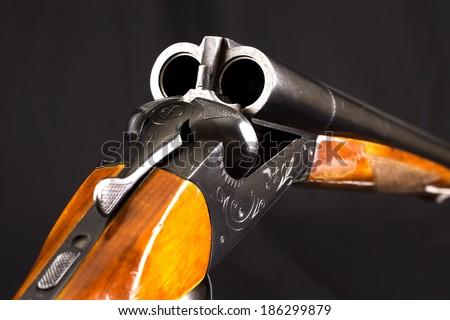 Opened double-barreled hunting gun against black - stock photo