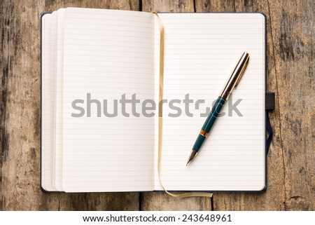 Opened empty notebook with retro fountain pen on wooden table. Writing background - stock photo