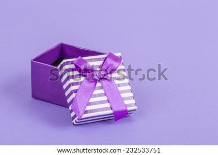 opened gift box on purple - stock photo