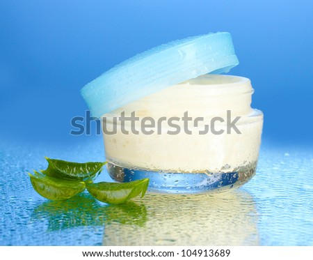 Opened glass jar of cream and aloe on blue background with water droplets - stock photo