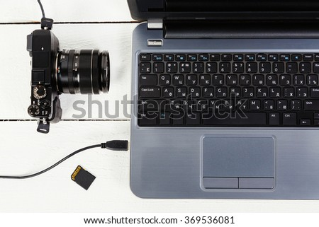 Opened gray laptop with connected photo camera and micro card on white wooden table, point of view, close up.