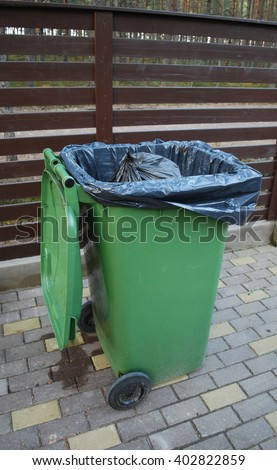 Opened green dumpster on brown wooden fence background. Black bag of trash with strings is inside dumpster.