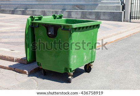 Opened green plastic recycling container at the sunny city street - stock photo