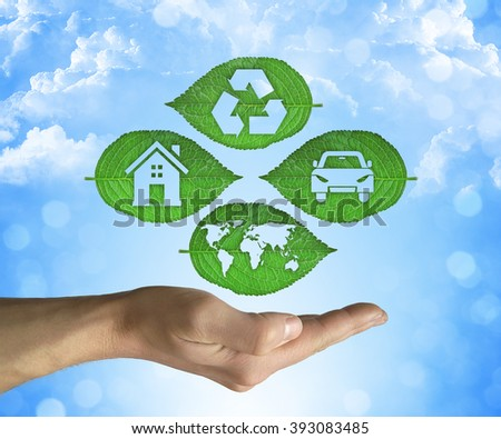Opened hand holding a green leaf with recycling symbol on a blue sky background. Friendly environment and sustainable development and eco world concept - stock photo