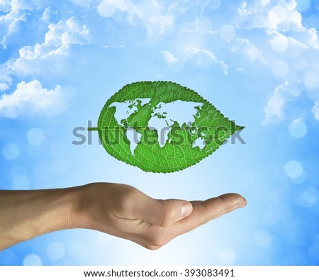 Opened hand holding a green leaf with world map inside on a blue sky background. Eco world concept - stock photo