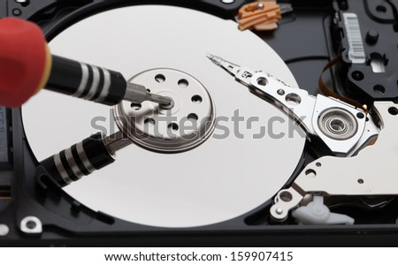 Opened hard disk and screwdriver - stock photo
