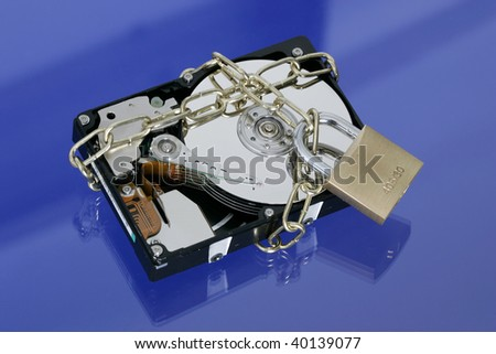 Opened hard disk secured with an iron chain and padlock on blue background - stock photo