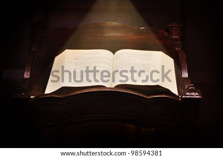 Opened holy Bible book lying on a pew in the church illuminated by ray of light