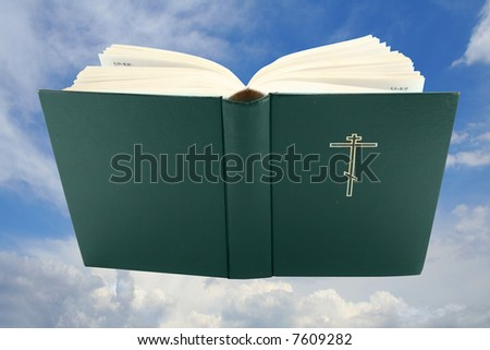 Opened holy bible over sky with clipping path, isolated - stock photo