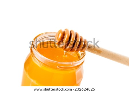 opened honey jar with wooden honey dipper on top pouring honey, isolated on white background - stock photo