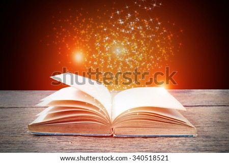 Opened magic book on abstract red gold background